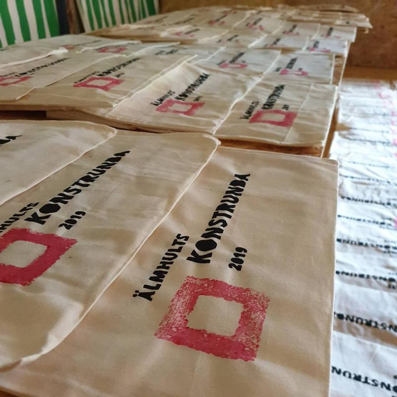 Massa naturfärgade textilväskor som ligger på tork med Älmhults konstrunda 2019 logga