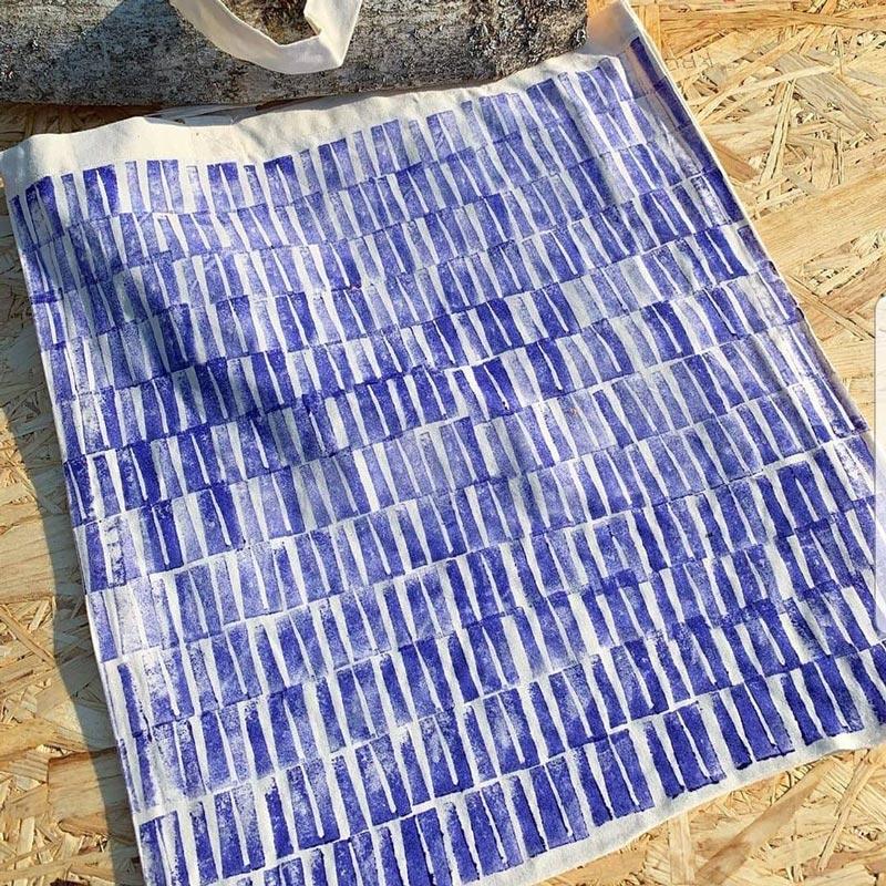 Textilväska som ligger och torkar i solen med blåa ränder