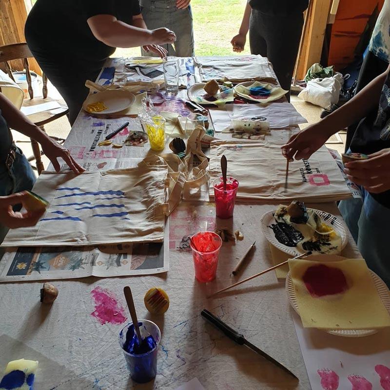 Bord med färg och penslar och handtryckta textil väskor