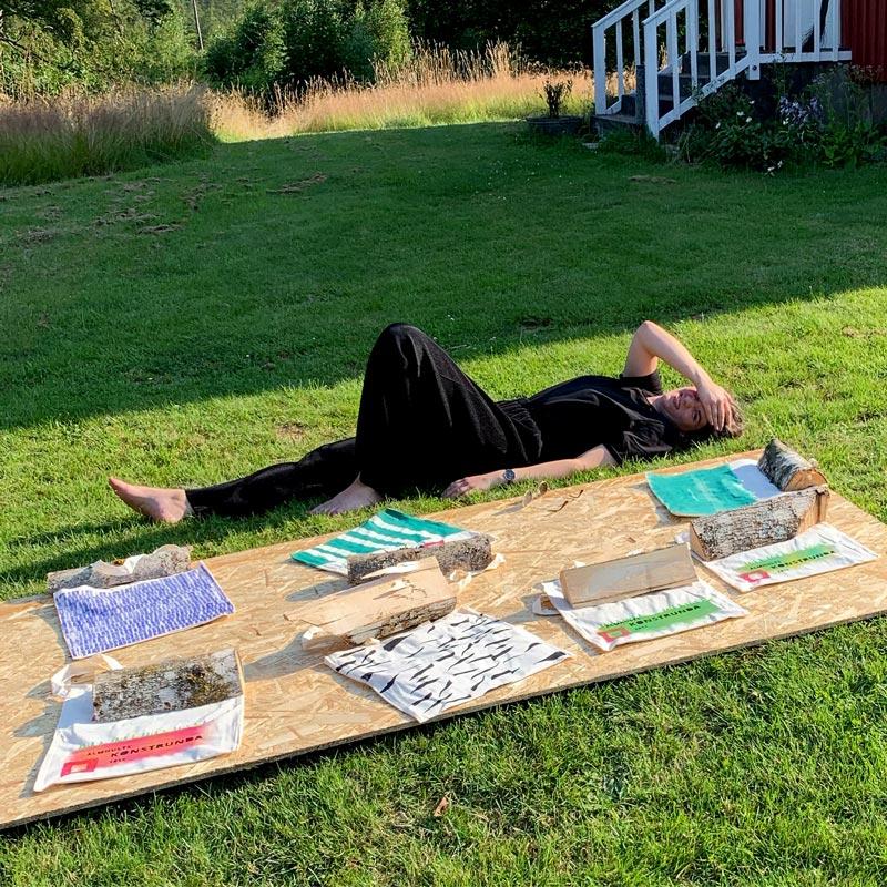 Konstnären Alinde Jormfeldt ligger i gräset och vaktar handtryckta ekologiska textil väskor som torkar i solen