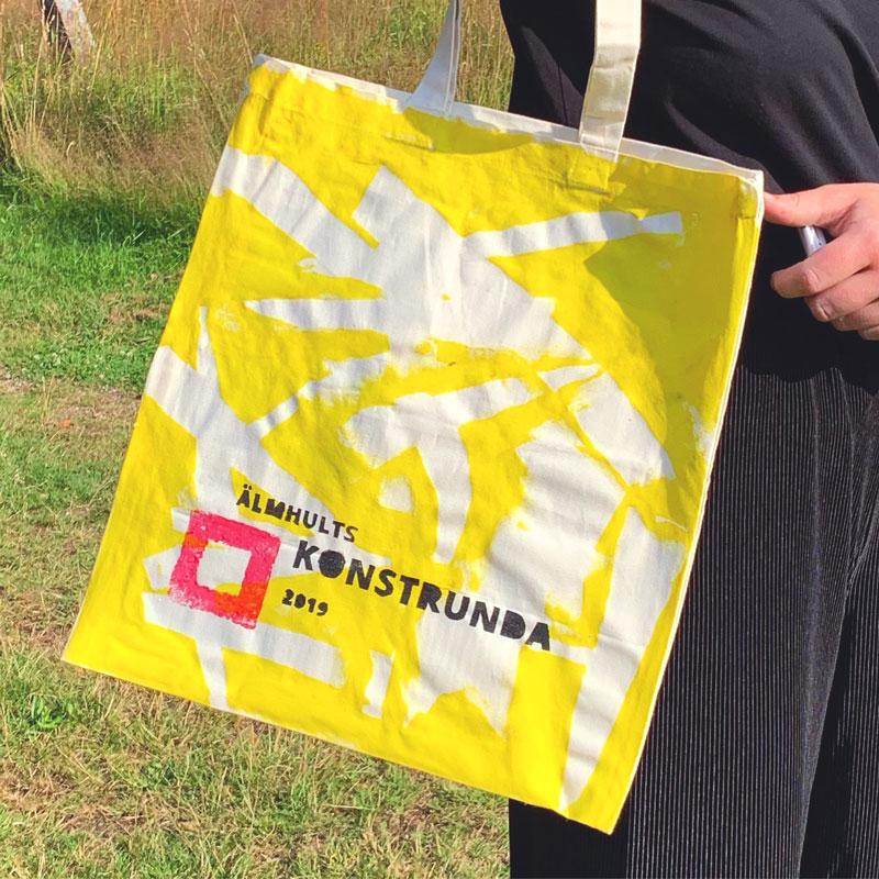 Tygväska med handtryckt gult abstrakt mönster och Älmhults konstrunda 2019 logga
