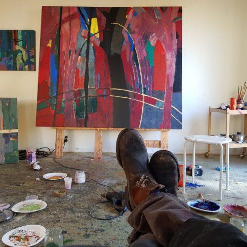 Konstnären Arne Persson har lagt upp fötterna och beundrar sitt konstverk i rött