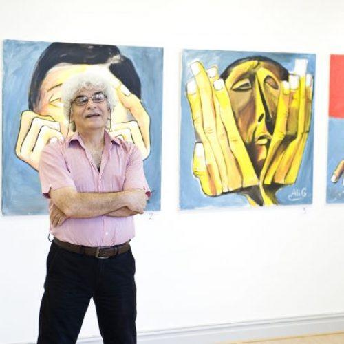 Bild på konstnären Ali Aljounde framför hans tavlor med gula människor och stora händer